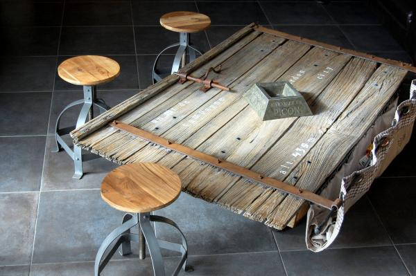 Los taburetes lateques industriales encajan perfectamente con la vieja puerta del establo de nuestro establo de Limousine transformado en una mesa de centro.