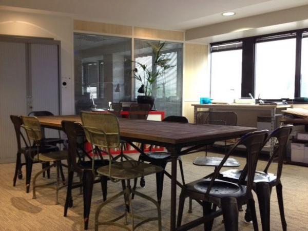 Un lugar cómodo para reunirse con la gran mesa de papel pintado, sillas Multipl, y sillas industriales perforadas