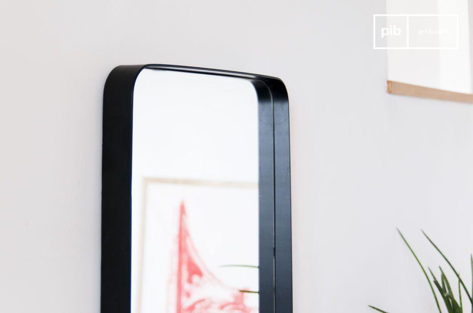Un gran espejo con marco negro, con un estilo discreto pero enérgico.