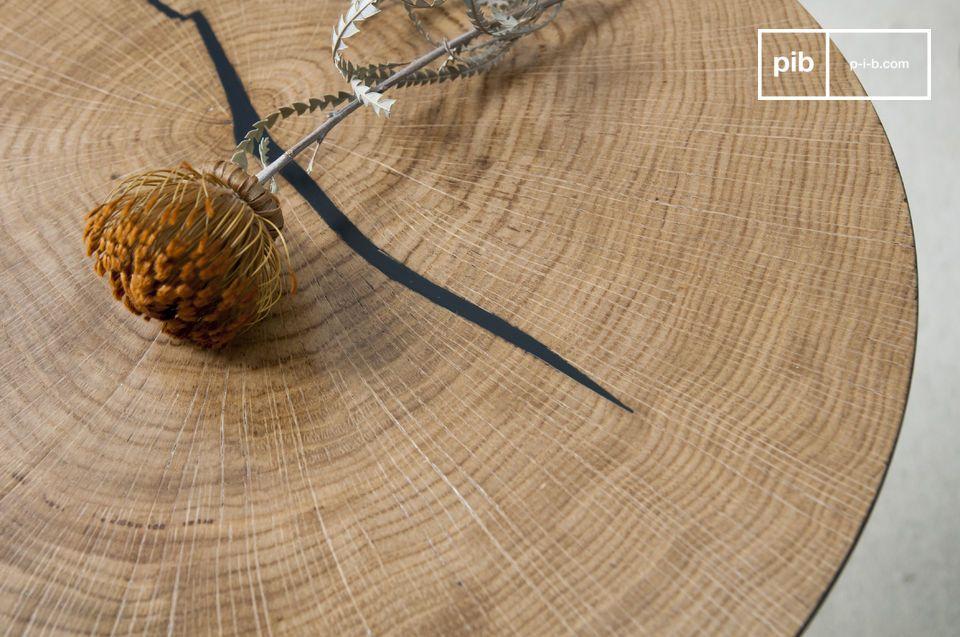 La hendidura natural de la pieza de madera se ha rellenado de negro y hace eco del color del pie