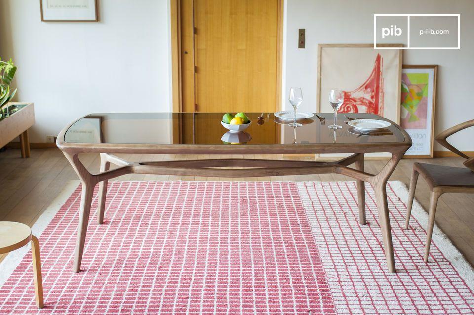Elegante y refinada, la mesa de comedor Iniö se compone de una base de ceniza maciza barnizada mate