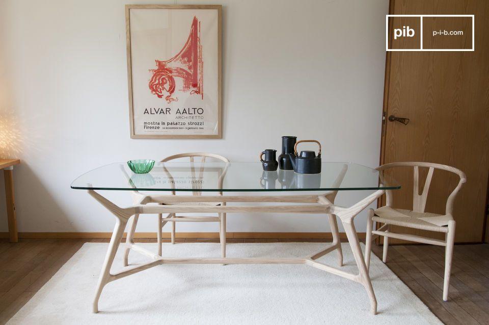 Una mesa de comedor de vidrio y madera clara con un espíritu nórdico vintage