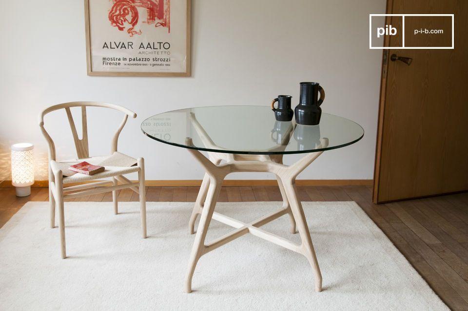 Una mesa redonda en recovecos y transparencias, combinando madera maciza y vidrio templado