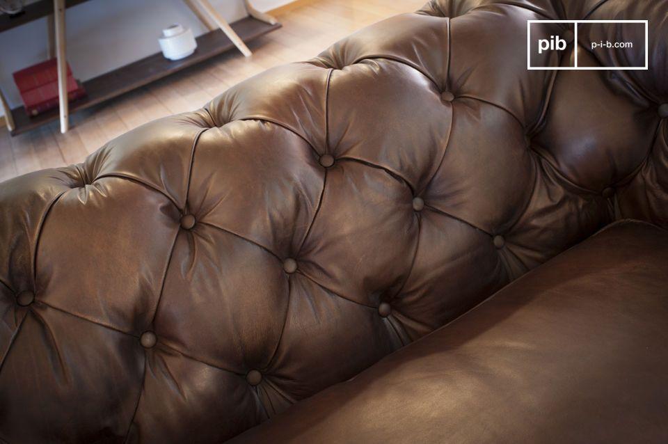 El sofá oscuro Chesterfield cabe fácilmente en su sala, dándole un estilo country club